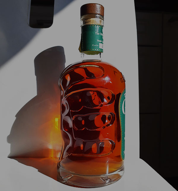 Artsy picture of hand holding German whisky bottle